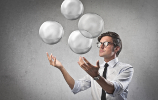 Businessman juggling with some air bubbles